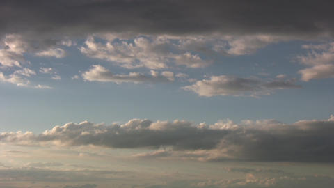 Timelapsed clouds slowly drift amidst a blue sky (High... Stock Video Footage