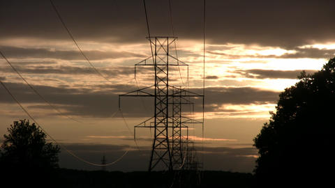 Hydro towers silhouette drifting orange clouds amidst sunset (High Definition) Footage
