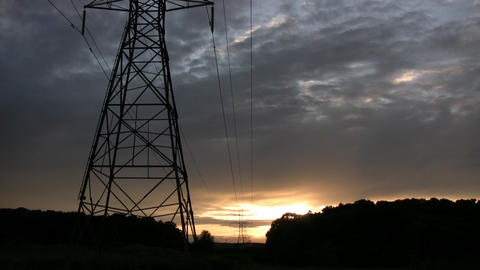Hydro towers silhouette drifting orange clouds amidst... Stock Video Footage