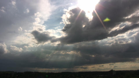 Clouds are slowly drifting as sunbeams pierce through (High Definition) Footage