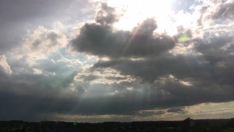 Clouds are slowly drifting as sunbeams pierce through... Stock Video Footage