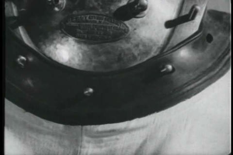 The breastplate of a deep sea diving suit is discu Live Action