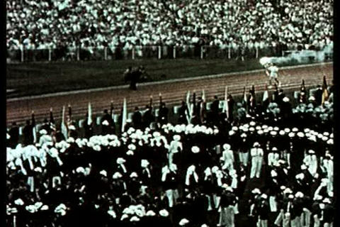 A runner lights the ceremonial olympic torch durin Footage