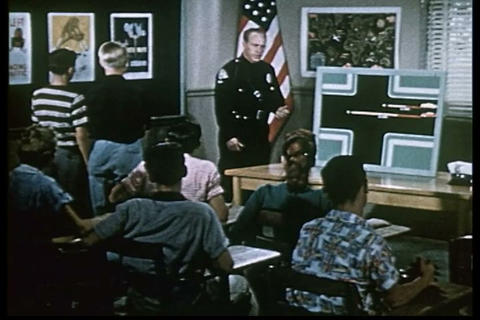 A police officer lectures a class of young men and Live Action
