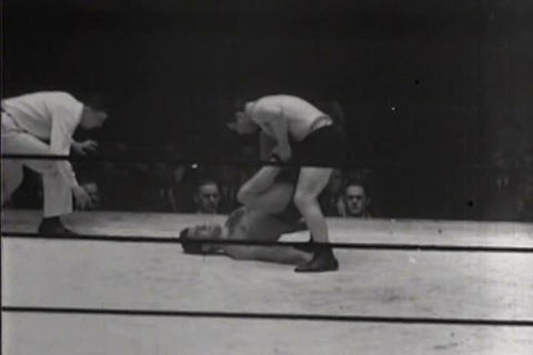 Wrestlers compete in a ring in 1931 Live Action