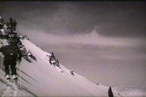 Men cross a dangerous snowfield and an avalanche b Footage