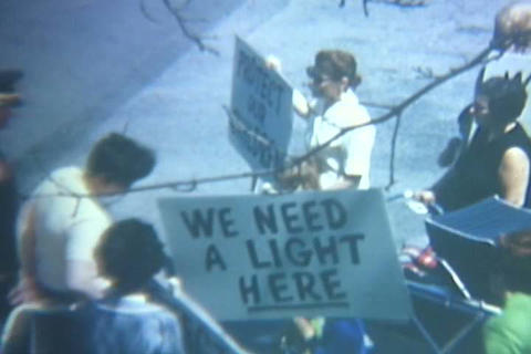 Protestors gather around a school in the 1960s Stock Video Footage
