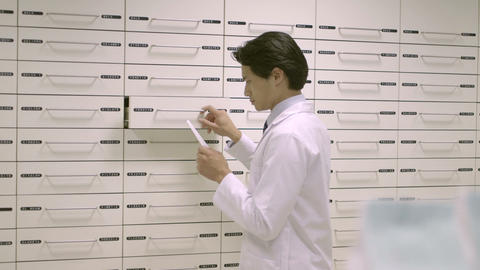 Male pharmacist in pharmacy searching medicine in drawer Live Action