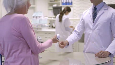 Pharmacist giving pill bottle to women Footage