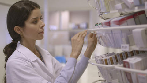 Female pharmacist searching medicine in pharmacy Footage