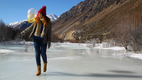 Happy young girl with balloons walking on ice Footage