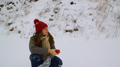 Young Girl Eating Apple And Sitting In The Snow stock footage