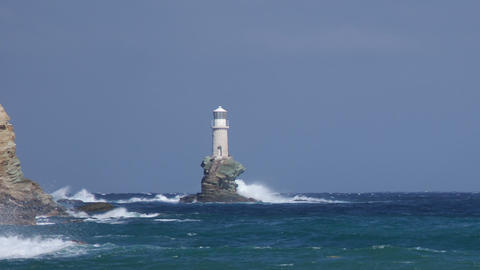 Lighthouse on the rock in stormy sea under waves Footage