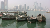 Fishing boats in front of skyline in China Footage