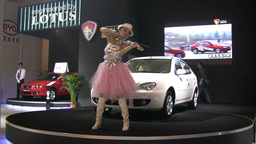 Chinese lady dancing at car show, playing violin Footage