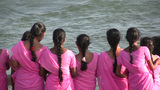 Indian pilgrims in pink dress watch waves Footage