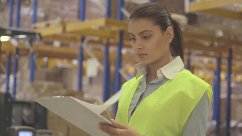 Young woman engineer standing and holding clipboard in factory warehouse ライブ動画