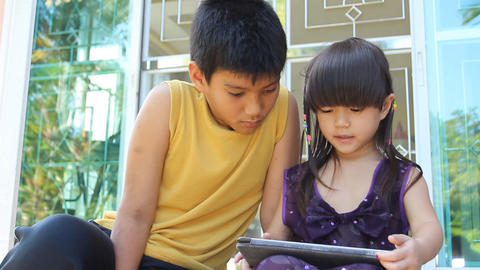 Asian boy and girl using tablet PC together Footage