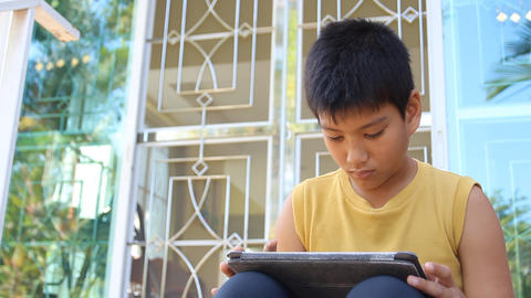 young boy using a digital tablet Live Action