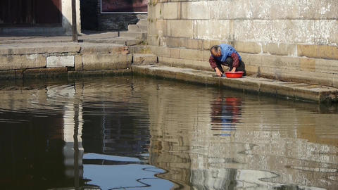 chinese old woman wash cloths under bridge,china water town life Animation