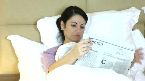 Woman Reading Newspaper Lying On Bed At Home stock footage