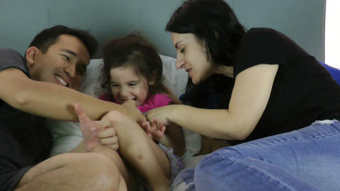 Parents tickling their child on bed at home Footage