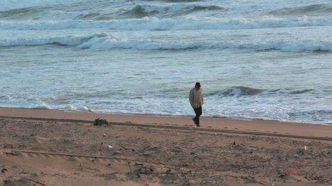 Man walking on the beach with storm waves at sunse Footage