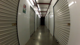 POV Moving Down Long Hall Past Storage Units stock footage