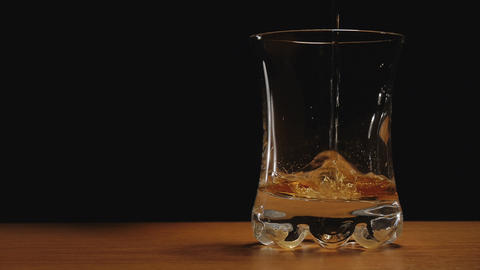 Liquor or whiskey poured in a glass against black  Footage
