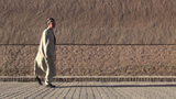 Senior Uzbek Man Walks Past Wall Of Silk Road City stock footage