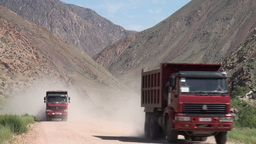 Construction trucks drive over dusty road Kyrgyzst Footage