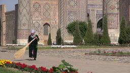 Lady Sweeping In Front Of Registan Samarkand stock footage