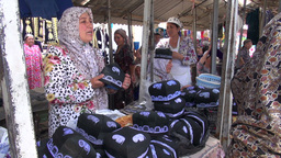 Veiled lady sells muslim hats in Uzbekistan Footage