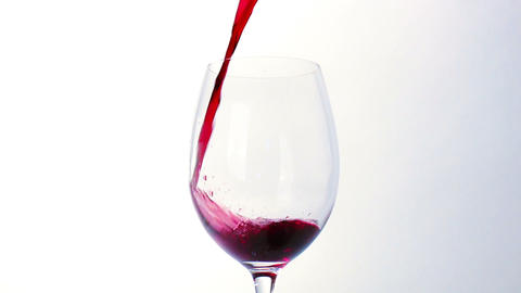 Red wine poured into glass on white background Footage