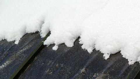 On a black roof snow melts. Time Lapse Footage