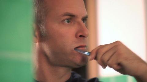 Toothbrush with man brushing teeth in home bathroom Footage
