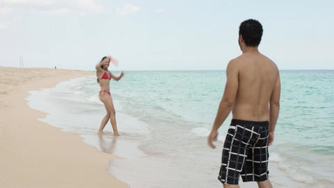 Couple playing Frisbee ON The Beach Footage
