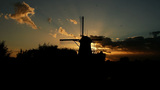 Silhouette Of A Windmill At Sunset And A Swarm Of  stock footage