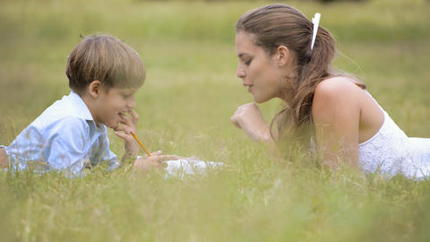 Mom Helping Son With Homework Lying On Grass At Pa stock footage