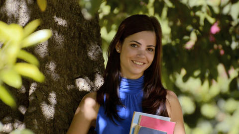 Portrait of young woman leaning with university bo Footage