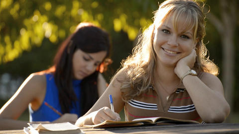 Two young women studying with textbook for college Footage