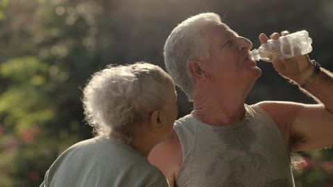 Seniors Drinking Water After Fitness In Park stock footage