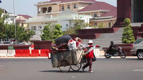Woman pulls a cart along the main street of Phnom  Footage
