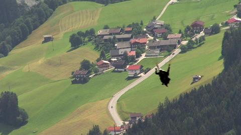 paraglider over austrian village Stock Video Footage
