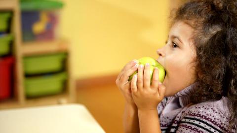 Child Eating Green Apple in Kindergarten Footage