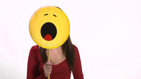 Woman holding yawning face emoticon Stock Video Footage