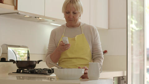 Senior Woman At Phone And Cooking Stock Video Footage