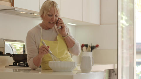 Senior Woman At Phone And Cooking Footage