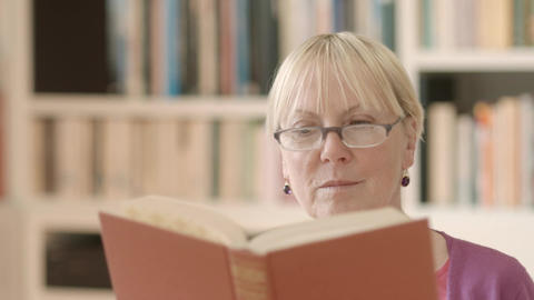 Senior woman reading book at home Footage
