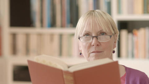 Senior woman reading book at home Stock Video Footage